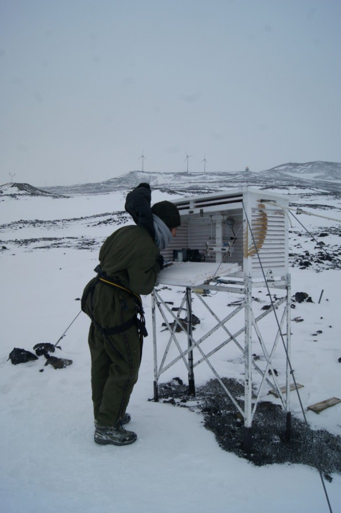 Kate from Antarctica New Zealand making the temperature observations at Scott Base. In the background the three wind turbines installed on Crater Ridge behind Scott base in 2010 are just visible.