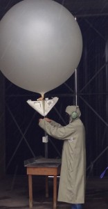 Contractor fits reflector and radiosonde to inflated balloon.