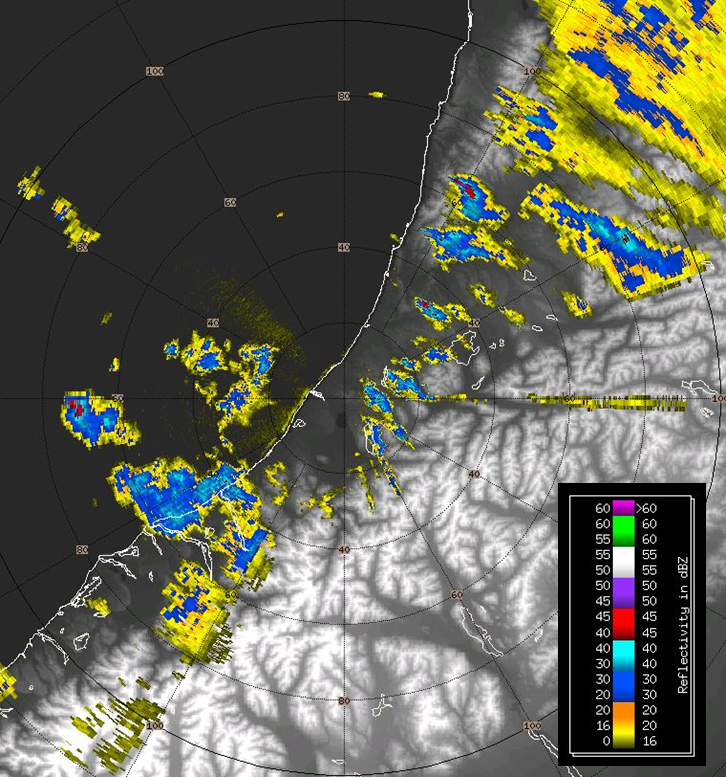 Figure 1: A 'plan position indicator' (PPI) view of the Westland weather radar. The radar is situated at the centre of the concentric rings. The rings show distance from the radar and are spaced every 20 km. This weather radar image shows precipitation reflectively (units are dbZ). Yellow and blue colours indicate light to moderate showers respectively, while red/purple colours indicate heavier precipitation. Note the heavy shower located almost 75 km due west of the radar and another 65 km to the NNE. Note that because the beam angles up as distance from the radar increases, some lower-level precipitation may not be seen – it quite literally lies 'under the radar'.